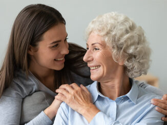 young woman embracing senior woman