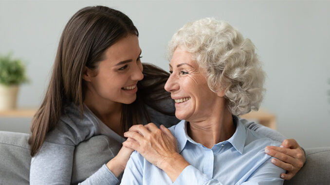 young woman embracing senior woman