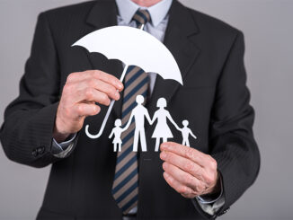 paper cut out family under umbrella