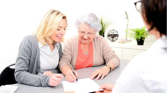 senior woman and younger woman looking over paperwork